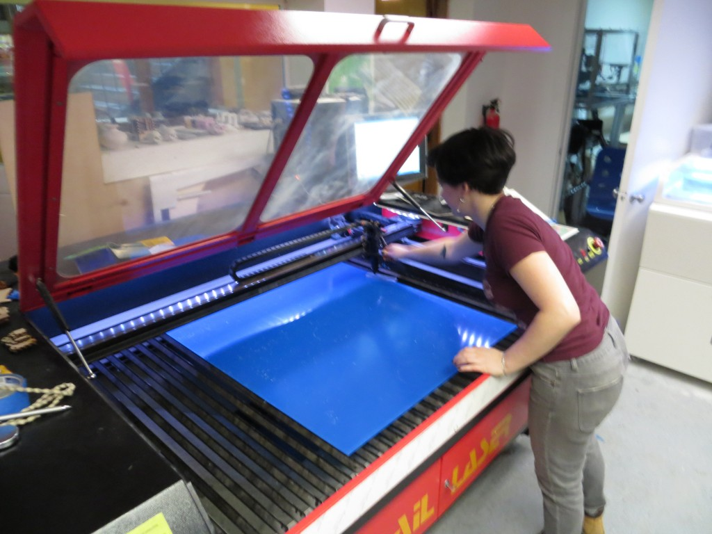 Lauren loads my sheet of acrylic into the laser cutter.