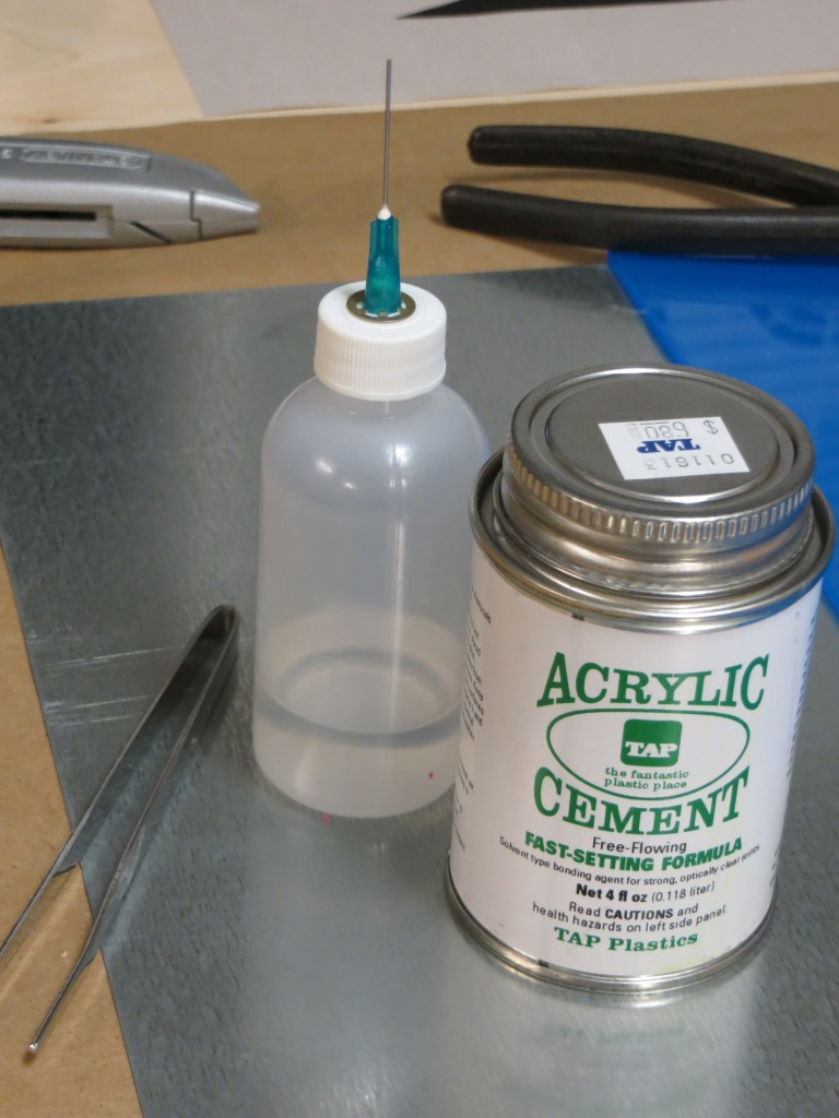 I am using acrylic cement from TAP Plastics to assemble the plate. The syringe bottle shown on the left is a huge help in spreading the cement and containing the fumes. The great thing about the syringe is that you can run it along the joints and they will draw in the cement through capillary action.