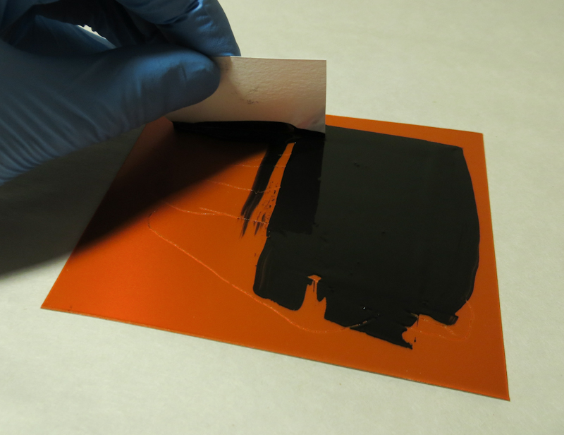 The first step in printing intaglio is to apply ink to the plate. I like to use a scrap of cardstock to help push the ink into all of the grooves.